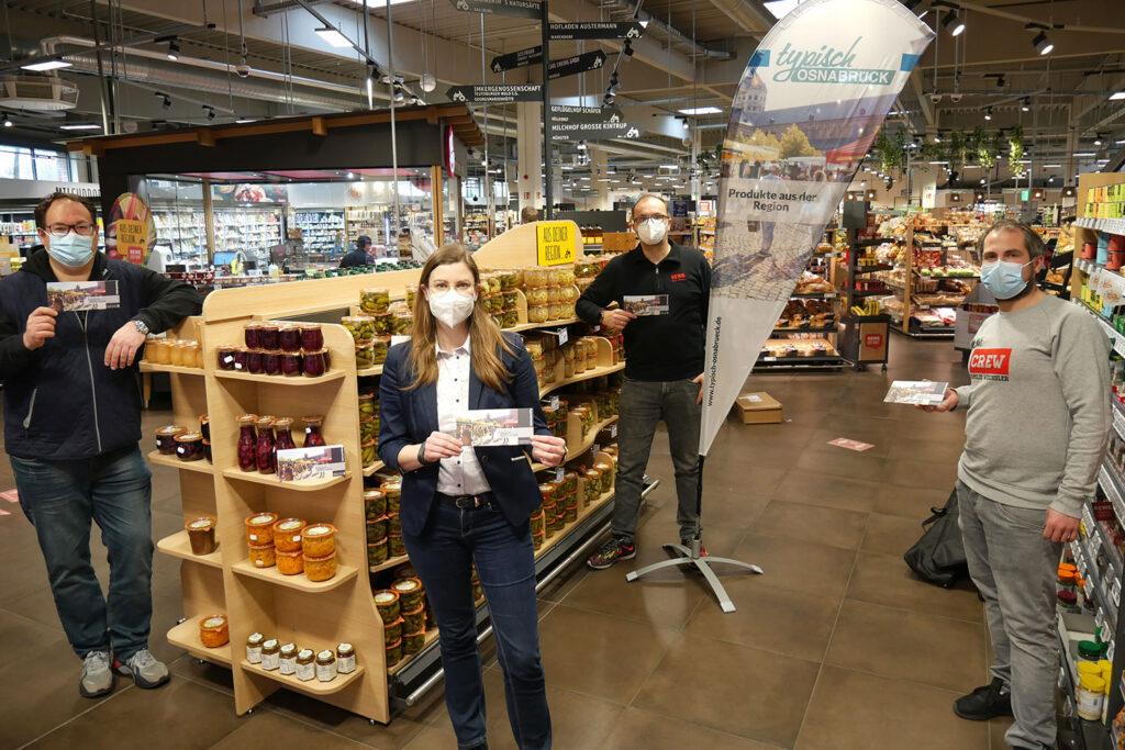 """V.l.n.r.: Jens Kaluscha (REWE), Britta ten Haaf (WFO Wirtschaftsförderung Osnabrück), Oliver Wehling und Jens Wechsler (beide REWE) installierten die neue Markenpräsenz """"Typisch Osnabrück"""" im REWE-Markt Blankenburg in Hellern."""